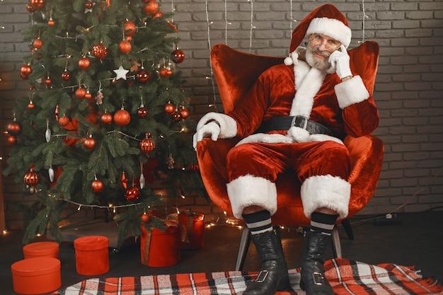 Der weihnachtsmann ruht sich am weihnachtsbaum aus. haus dekoration.