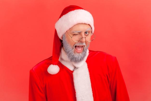 Der weihnachtsmann schaut in die kamera und zwinkert, ist in festlicher stimmung und freut sich über den kommenden urlaub.