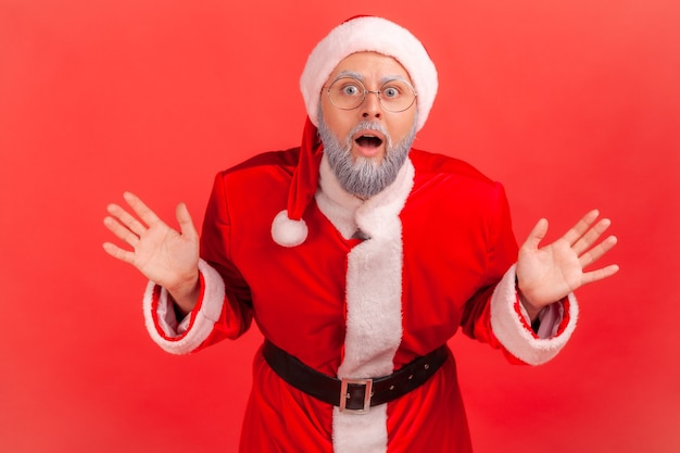 Der weihnachtsmann schaut mit offenem mund in die kamera, schreit mit überraschtem gesicht, erhobenen armen