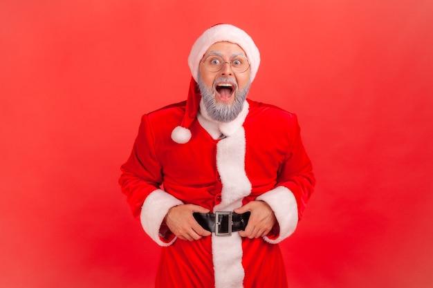 Der weihnachtsmann schaut mit schockiertem gesichtsausdruck in die kamera und hält die hände am gürtel