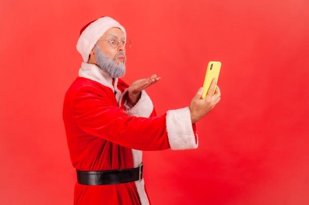 Der weihnachtsmann schickt seinen anhängern luftkuss, während er einen livestream sendet oder ein selfie macht.