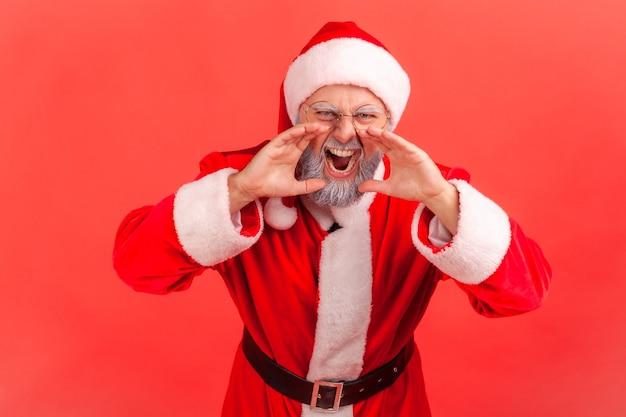 Der weihnachtsmann schreit mit wütendem gesichtsausdruck und hält die hände in der nähe des mundes.