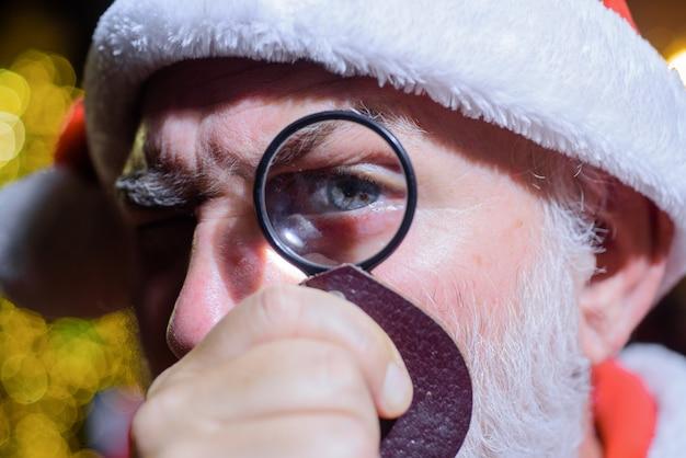 Der weihnachtsmann sieht durch die linse bärtiger mann in weihnachtsmütze hält lupe weihnachtsmann, der durchschaut