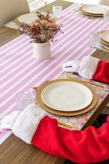 Der weihnachtsmann sitzt am tisch und ist fertig zum essen