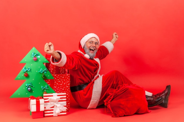 Der weihnachtsmann sitzt auf dem boden und hob die arme in der nähe von geschenkboxen und dekorativem papierweihnachtsbaum.