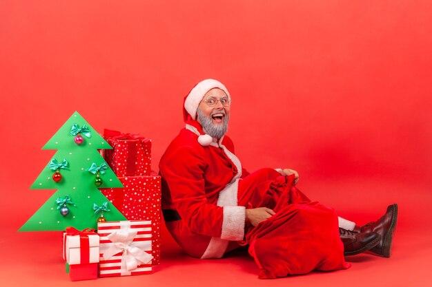 Der weihnachtsmann sitzt auf dem boden unter einem geschmückten weihnachtsbaum mit geschenkboxen und einer großen roten tasche