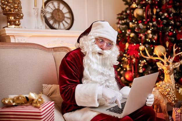 Der weihnachtsmann sitzt bei ihm zu hause und liest e-mails auf einem laptop mit weihnachtsanfragen oder wunschliste in der nähe des kamins und des baumes mit geschenken. frohe weihnachten, frohe feiertagskonzept