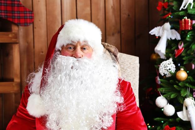 Der weihnachtsmann sitzt in einem bequemen schaukelstuhl in der nähe von weihnachten zu hause