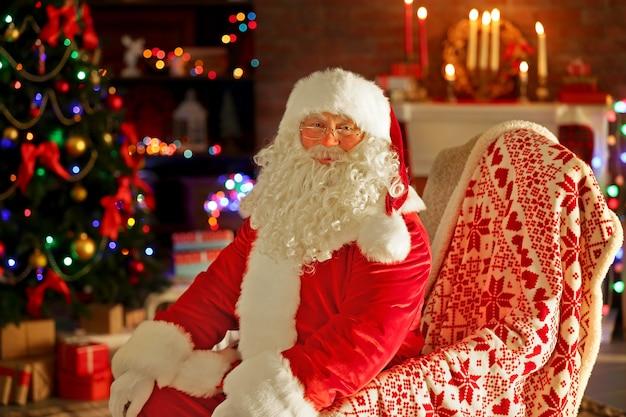 Der weihnachtsmann sitzt in einem bequemen stuhl in der nähe des kamins zu hause