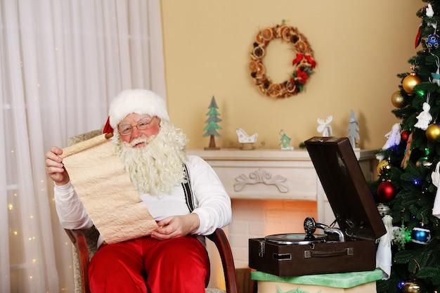 Der weihnachtsmann sitzt mit einer liste von kinderwünschen in einem bequemen stuhl in der nähe des kamins zu hause