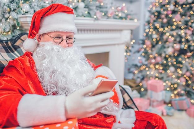 Der weihnachtsmann sitzt und schaut auf das telefon