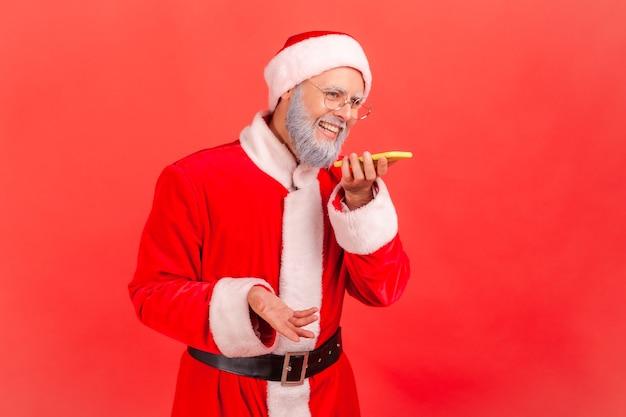 Der weihnachtsmann spricht mit dem telefon über eine digitale sprach-app, um daten im internet zu suchen.