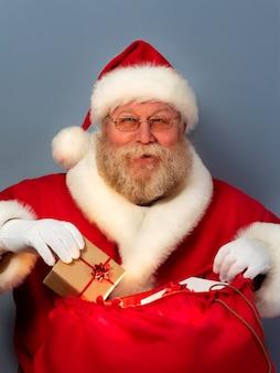 Der weihnachtsmann steckt die geschenkbox in seinen großen roten sack. weihnachtsfeier, wunder, geschenk an gutes und nettes kinderkonzept.