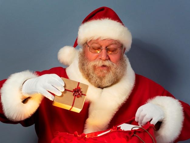 Der weihnachtsmann steckt die geschenkbox in seinen großen roten sack. weihnachtsfeier, wunder, geschenke an gute und nette kinder konzept.