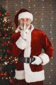 Der weihnachtsmann steht am weihnachtsbaum. haus dekoration.
