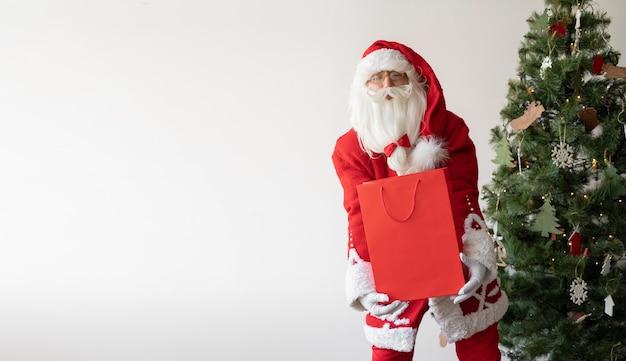 Der weihnachtsmann steht in der nähe des weihnachtsbaums und hält eine große einkaufstasche.