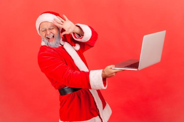 Der weihnachtsmann steht mit dem computer in der hand, sieht schreckliche inhalte auf dem bildschirm und bedeckt das gesicht.