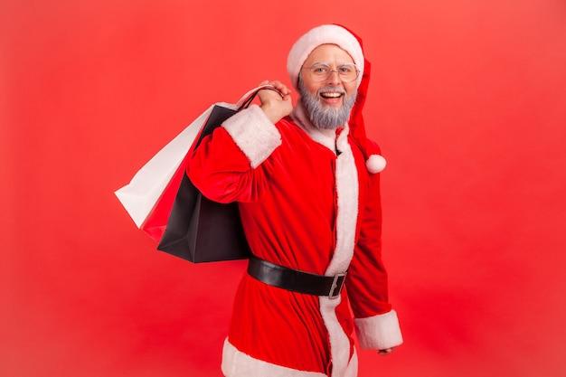 Der weihnachtsmann steht mit einkaufstüten und kauft ein geschenk für den winterurlaub.