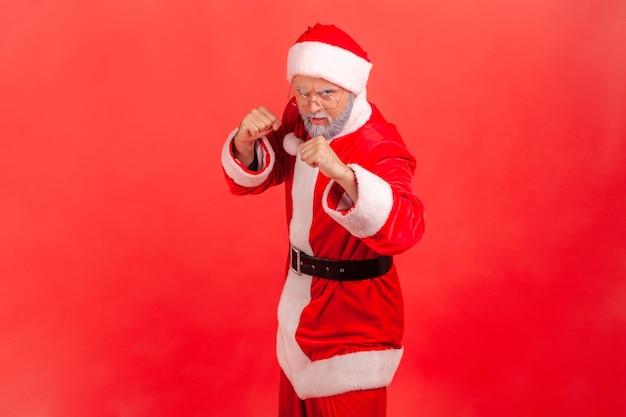 Der weihnachtsmann steht mit fäusten und ist bereit zu kämpfen und schaut mit wütendem ausdruck in die kamera.
