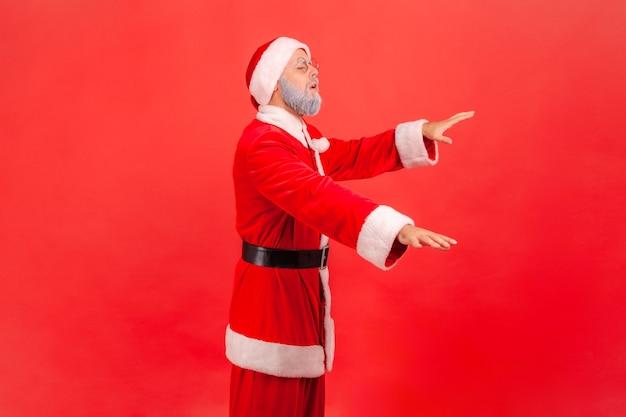 Der weihnachtsmann steht mit geschlossenen augen und versucht, etwas zu berühren.