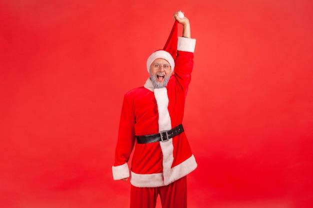 Der weihnachtsmann steht mit glücklichem ausdruck, der seinen hut hochzieht und mit erstaunen in die kamera schaut.