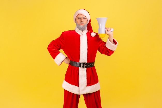 Der weihnachtsmann steht mit megaphon in den händen, schaut in die kamera und hält die hand auf der hüfte.