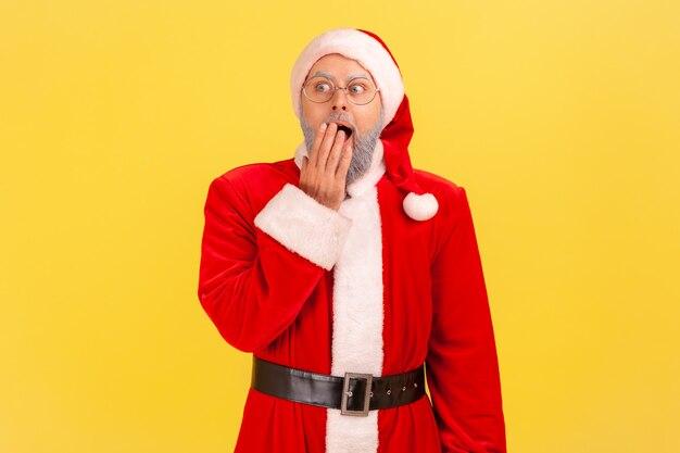 Der weihnachtsmann steht mit schockiertem ausdruck, bedeckt den mund und schaut weg.