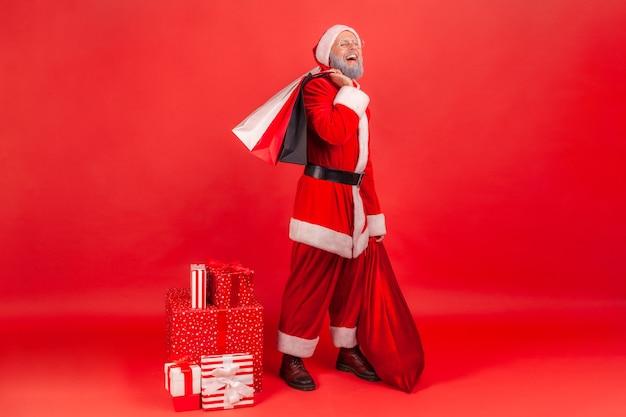 Der weihnachtsmann steht mit taschen mit geschenk- und weihnachtsgeschenken und blickt in die kamera.