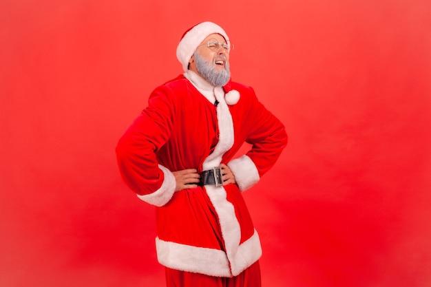 Der weihnachtsmann steht und hält die hände auf dem bauch, leidet an schmerzen, gastritis oder verstopfung.