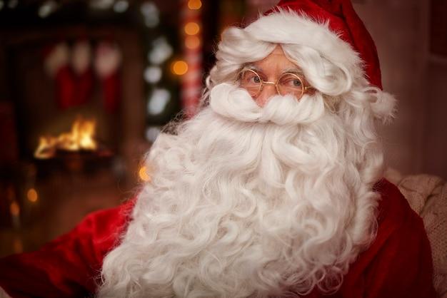 Der weihnachtsmann wärmt sich neben dem kamin auf
