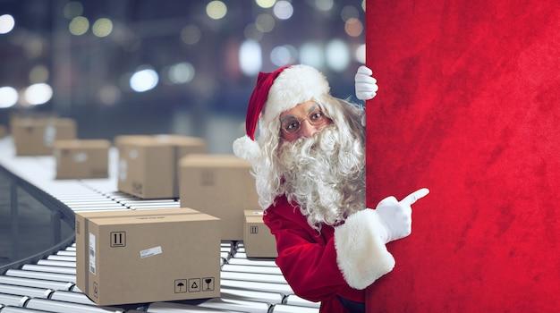 Der weihnachtsmann zeigt eine leerstelle für das weihnachtsgeschenk an, mit fertigen paketen im hintergrund