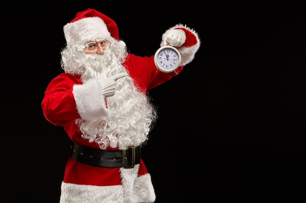 Der weihnachtsmann zeigt mit dem finger auf die uhr.