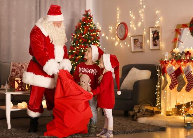 Der weihnachtsmann zeigt süßen kindern im zimmer mit schönen weihnachtsdekorationen geschenke