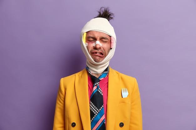 Der weinende unzufriedene mann hat nach schweren verletzungen gesundheitliche probleme, ist es leid, sich zu erholen, hat ein großes hämatom, fehlende zähne und einen verbundenen kopf. geschlagener patient mit blauen flecken auf lila wand isoliert.
