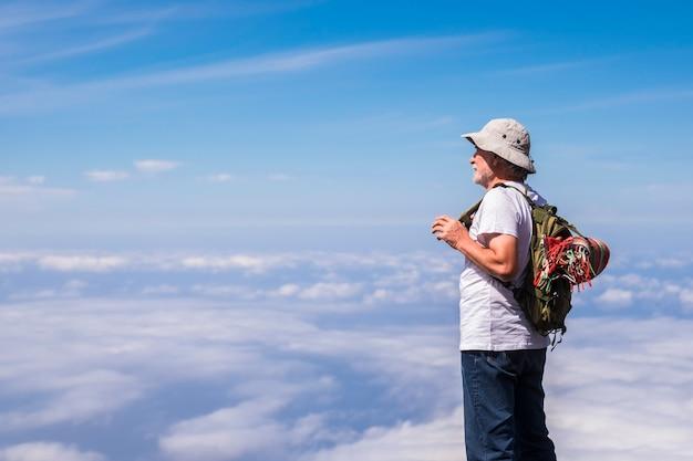 Der weiße haarmann der alten silbernen gesellschaft steht und ruht, schaut den blauen himmel unendlich vor sich und genießt die trekking-reise - konzept der freiheit im dritten alter für jugendliche im inneren