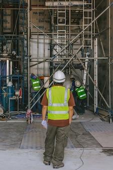Der weiße helm des ingenieurs trägt safty den bauplan auf der baustelle mit baugerüst
