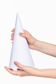 Der weiße kegel der requisiten in den weiblichen händen auf weiß mit rechtem schatten
