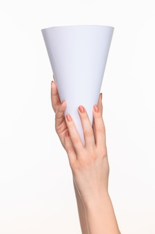 Der weiße kegel der requisiten in den weiblichen händen auf weißem hintergrund mit rechtem schatten