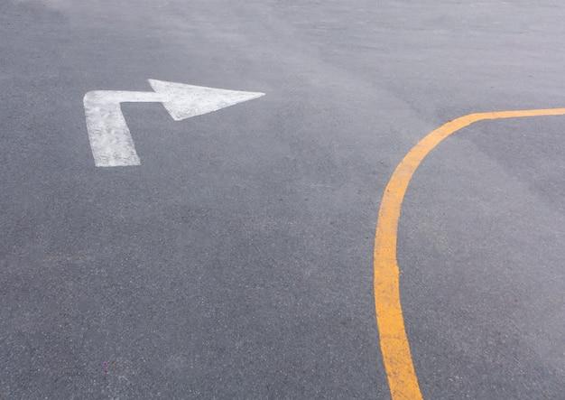 Der weiße pfeil auf dem boden mit gelber linie -