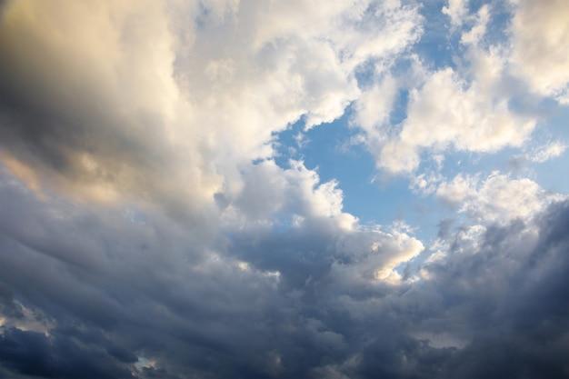 Der wind dreht weiß-blaue kumuluswolken an einem blauen himmel an einem sommerabend.