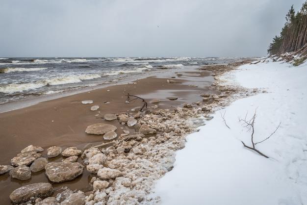 Der winterkalte ostseestrand ist schneebedeckt und es gibt große wellen im meer, in saulkrasti in lettland