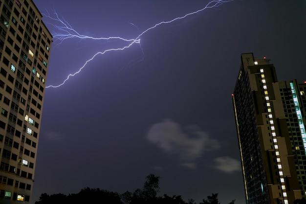 Der wirkliche blitz, der im nächtlichen himmel über hohen gebäuden von bangkok, thailand blinkt