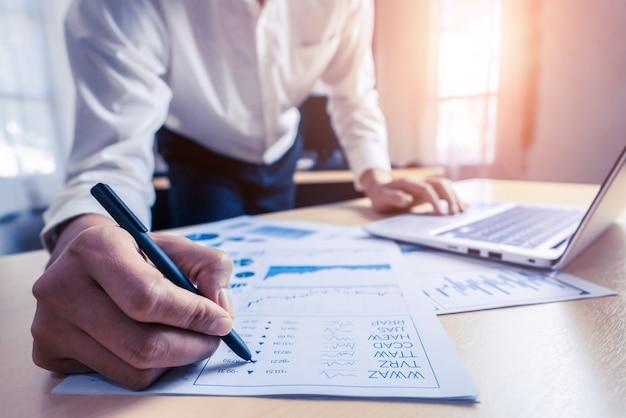 Der wirtschaftsprüfer oder finanzexperte analysiert das geschäftsberichtsdiagramm und das finanzdiagramm in der unternehmenszentrale.