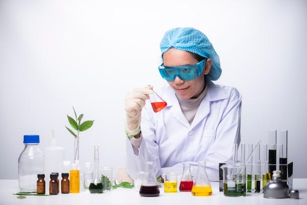 Der wissenschaftler, der im labor, in der schutzmaske und in der kappe arbeitet, überprüft ein reagenzglas mit flüssigkeit