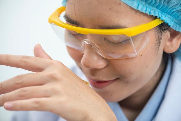 Der wissenschaftler, dermatologe, der das organische naturkosmetikprodukt im labor-, forschungs- und entwicklungsschönheits-hautpflegekonzept, leeres paket, flasche, behälter, creme, serum, hand prüft