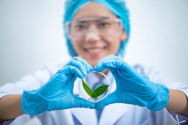 Der wissenschaftler, dermatologe, der das organische naturkosmetikprodukt im labor-, forschungs- und entwicklungsschönheits-hautpflegekonzept prüft