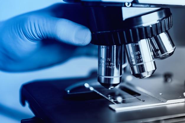 Der wissenschaftliche umgang mit einem lichtmikroskop untersucht eine laborprobe für die pharmazeutische biowissenschaftliche forschung. konzept der wissenschaft, labor und untersuchung von krankheiten.
