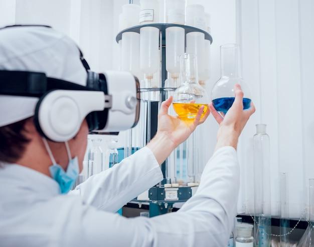Der wissenschaftstechniker in virtual-reality-brillen untersucht das medikament im labor.