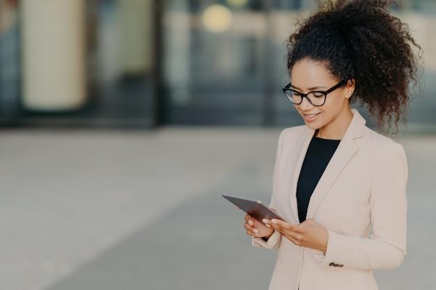 Der wohlhabende inhaber eines unternehmens steht mit einem digitalen touchpad, das sich auf den bildschirm konzentriert