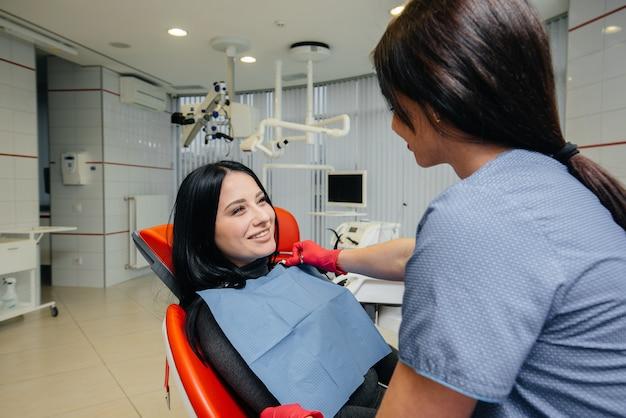 Der zahnarzt behandelt die patientenzähne für die patientin. zahnheilkunde
